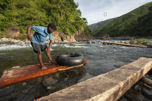 Luzon Island, Philippines - July 27, 2012: An Agta man floating hardwood down river from the Sierra Madre Mountains