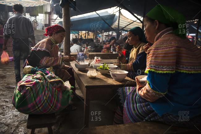 Bac Ha, Lo Cai, Vietnam - May 13, 2012: Hmong women eating at the Bac Ha Sunday Market