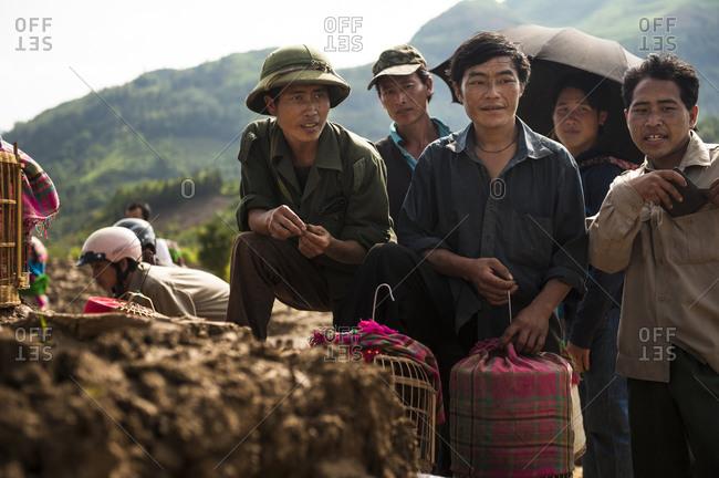 Bac Ha, Lo Cai, Vietnam - May 13, 2012: Hmong men observing song birds for sale at the Bac Ha Market