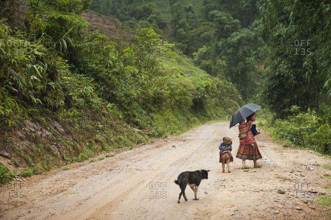 Sa Pa, Lo Cai, Vietnam - May 15, 2012: Hmong woman and her children walking along a road