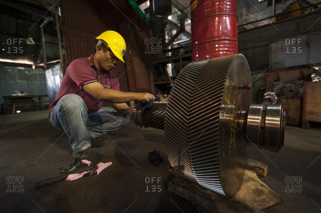 Visayan Island, Philippines - April 2, 2013: Man working on machinery in sugar mill