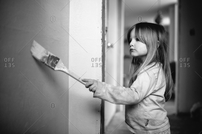 Young girl painting a wall