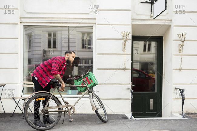 Man locking his locking bicycle on sidewalk outside candy store