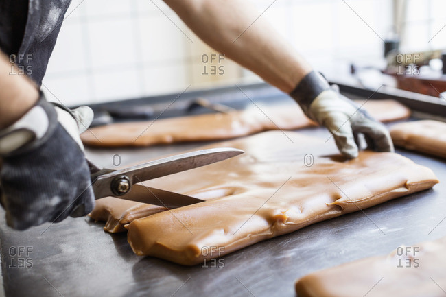 Worker cutting caramel with scissors in candy store