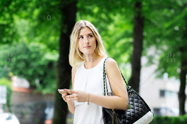 Young woman holding mobile phone while looking away outdoors