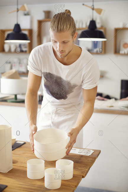 Young man holding craft products in crockery workshop