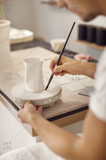 Young male worker painting pottery in crockery workshop