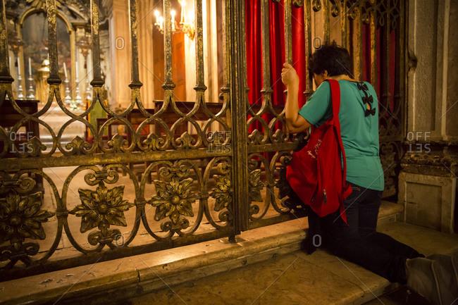Woman kneeled at Santissimo Sacramento chapel, Portugal
