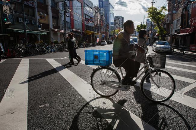 Osaka, Japan - April 21, 2013: Man riding a bicycle across a road