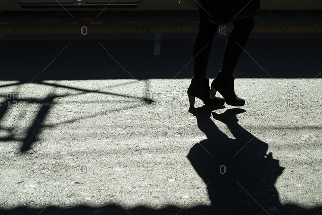 Lower legs and feet of a woman on a train platform, Nara, Japan