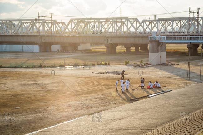 Osaka, Japan - December 28, 2013: Boys playing baseball on a dirt lot under a railway bridge, Osaka