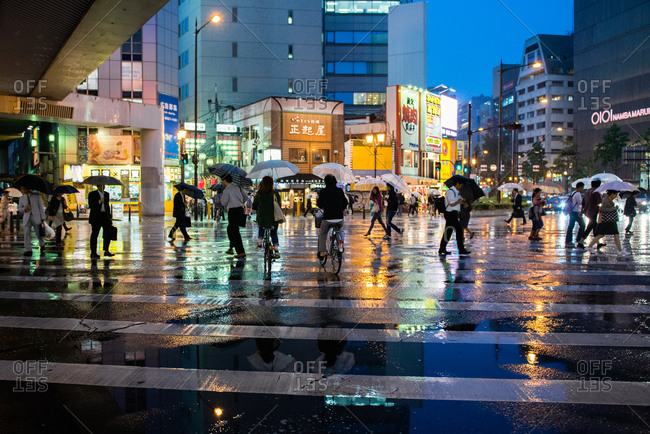 Osaka, Japan - May 20, 2014: Pedestrians and cyclists crossing street at busy urban intersection
