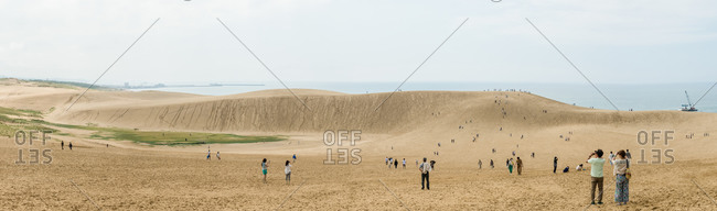 Sightseers on a large sand dune by the sea, Tottori, Japan