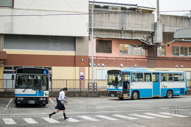 Tottori, Japan - June 9, 2014: Schoolgirl running past busses