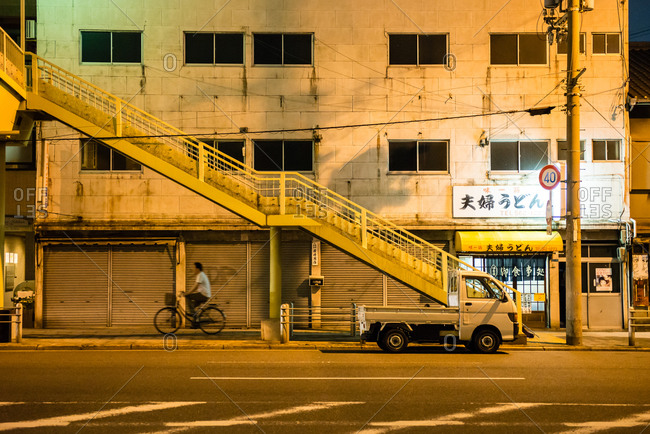 Osaka, Japan - June 28, 2014: Man riding bicycle on sidewalk by stairs