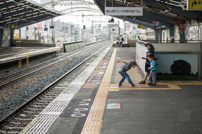 Sangenyahigashi, Osaka, Japan - July 20, 2014: Three young children playing on train platform in Osaka, Japan
