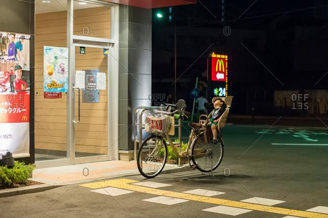 Osaka, Japan - July 25, 2014: Little boy asleep in bicycle child seat outside of McDonalds