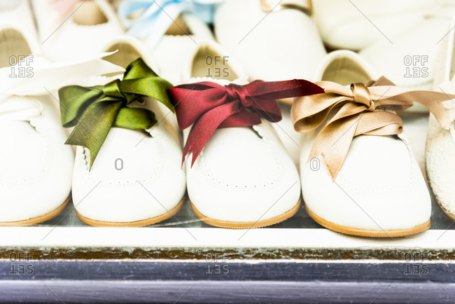 Small shoes with colorful ribbons on display