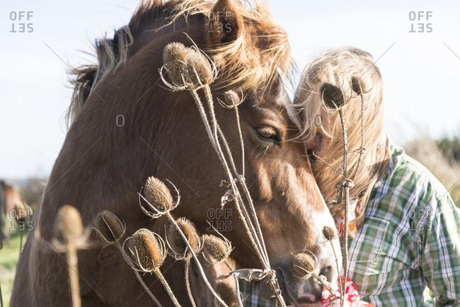 A woman nuzzles a horse