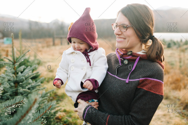 Mother and daughter choosing a Christmas tree at a plantation