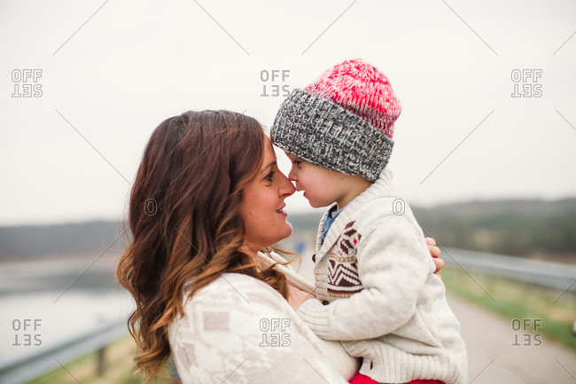 Mother holding her toddler son nose-to-nose