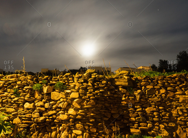 A stone wall and houses in the moon light