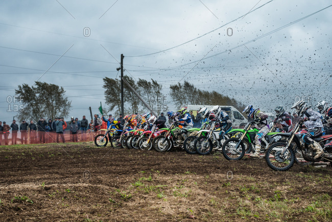 Motocross racers and onlookers at starting line