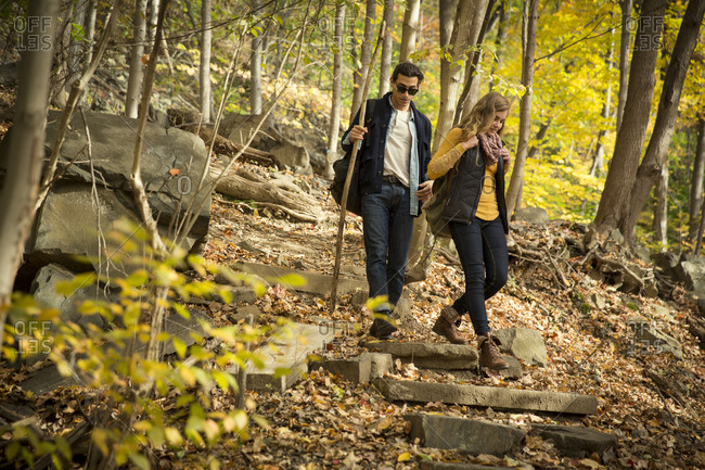 A couple hikes down a wooded trail