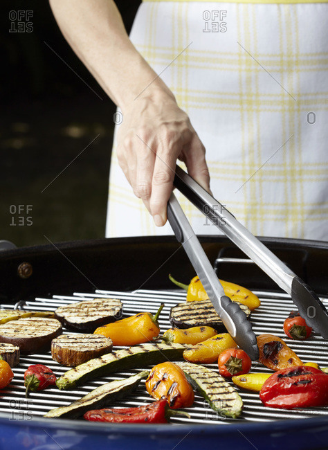 Close up of person grilling vegetables