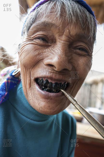 Yunnan, China - April 17, 2013: Old woman with black tooth smoking pipe, Yunnan, China