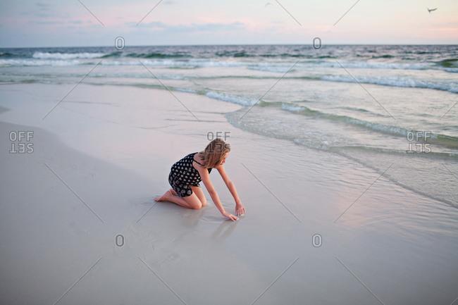 Girl kneeling in sand on beach
