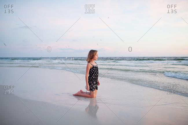 Girl kneeling and watching ocean