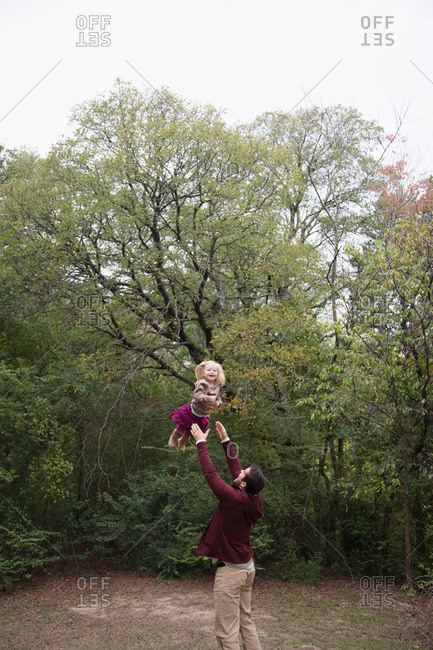 Man throwing girl in air outdoors in autumn