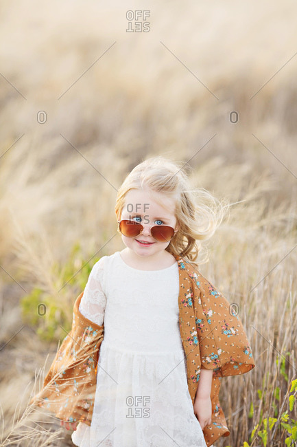 Girl with sunglasses in field