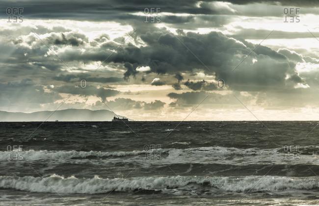 Ship on the ocean under cloudy sky