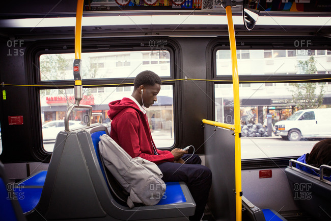 Teenage boy looking at his smartphone on a bus