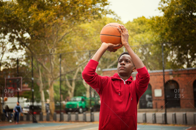 Teenage boy aiming a basketball on a court in New York City, USA