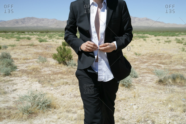 Man in disheveled suit in desert