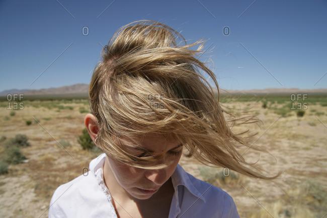 Portrait of woman in windy desert
