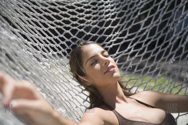 Woman laying in hammock in halter top