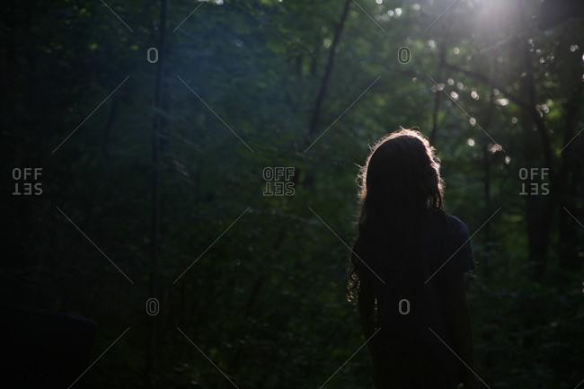 Girl in moonlit woods at night
