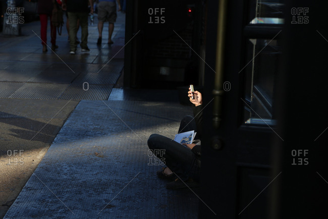 Woman sitting outside building alone