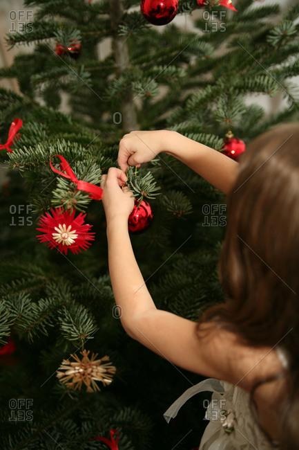 Girl putting holiday ornament on Christmas tree