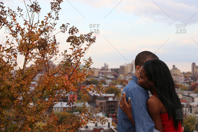 Young couple embracing with city view
