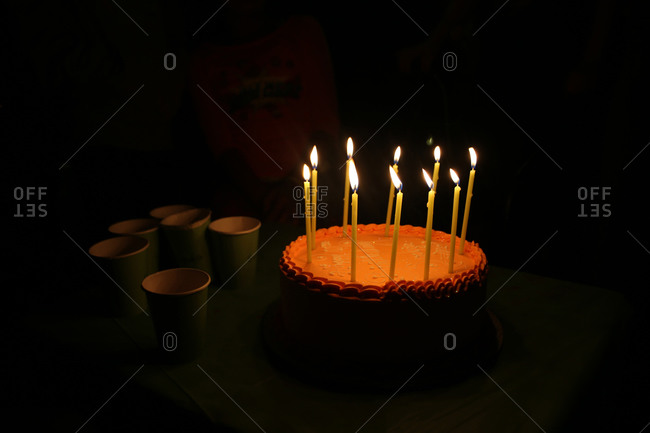 Birthday Cake Lit Up With Cups Stock Photo