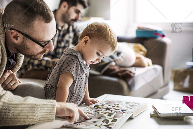 Father showing a picture book to his daughter