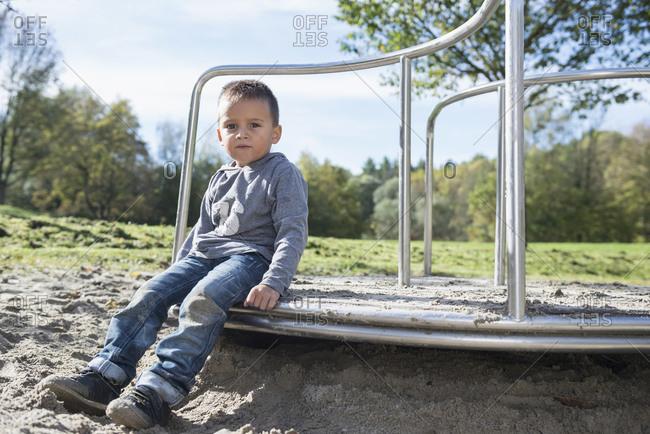 Boy playground sitting portrait sand carousel