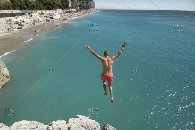 Boy holiday jump water ocean risk teenager