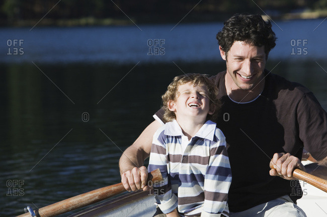 Father and son in rowing boat on lake laughing