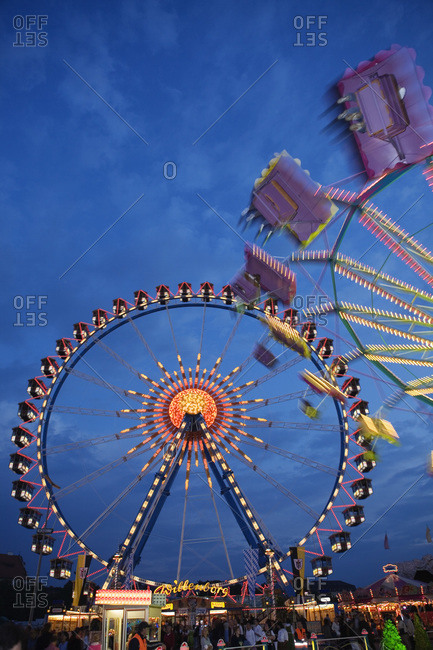 Illuminated fairground rides at night Oktoberfest Munich Germany